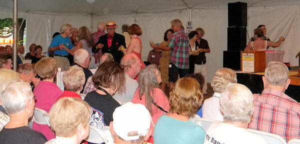 Full chairs in tent and busy dance floor