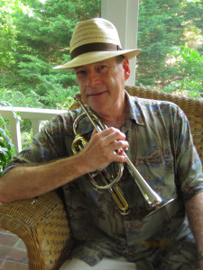 Jeff sitting at home in wicker chair on porch, Falmouth MA wearing, hawaiian shirt and straw hat, holding cornet