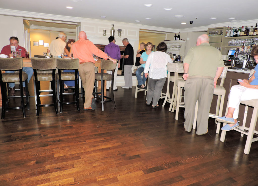 tall table to left, bar to right, shiny wooden dance floor in front