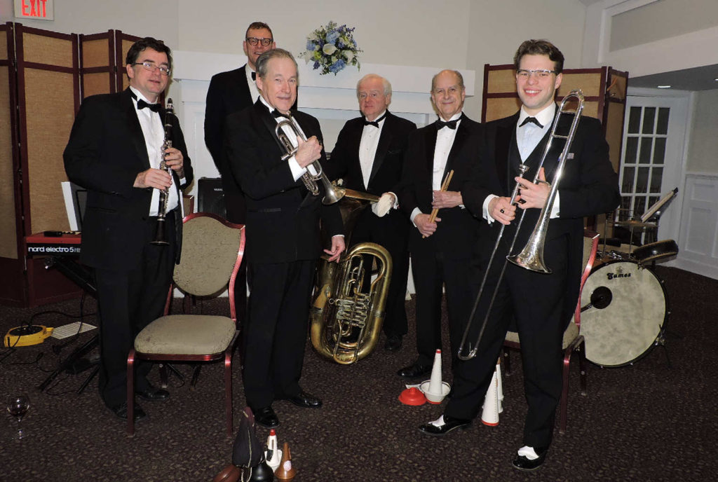 6 musicians standing in black tux and bow ties