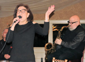 Elaine singing, left hand up in the air, Ted on tenor sax