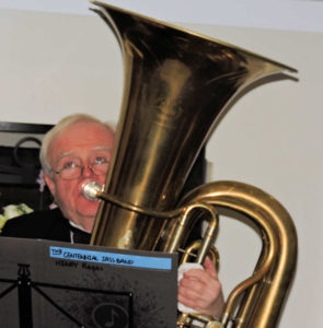 Rick sitting playing tuba, eyes looking up at ceiling