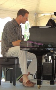 Ian Frankel, about 7 feet tall, sitting at the piano