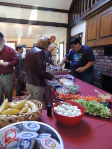 table filled with food and people helping themselvees