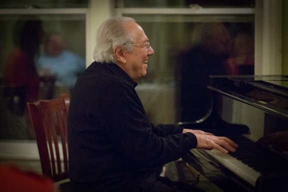 Bob Winter, smiling and playing piano
