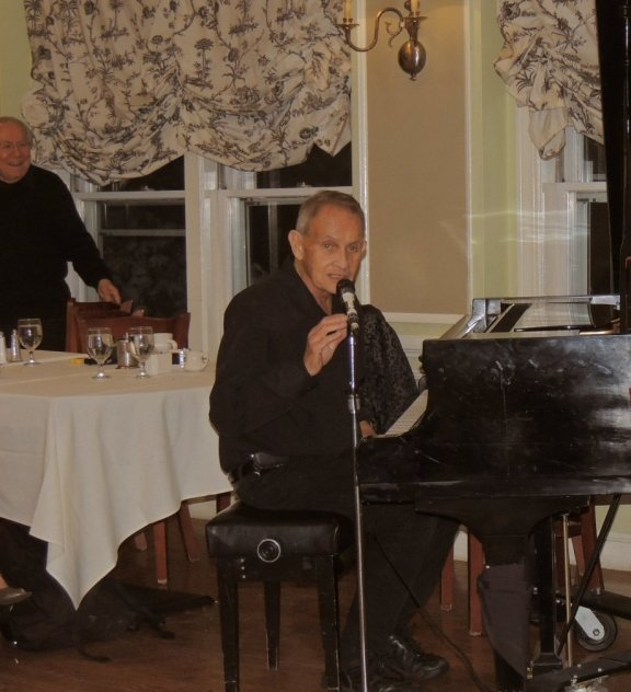 Herb Gardner at the piano, talking on mic, with Bob Winter smiling in the background.