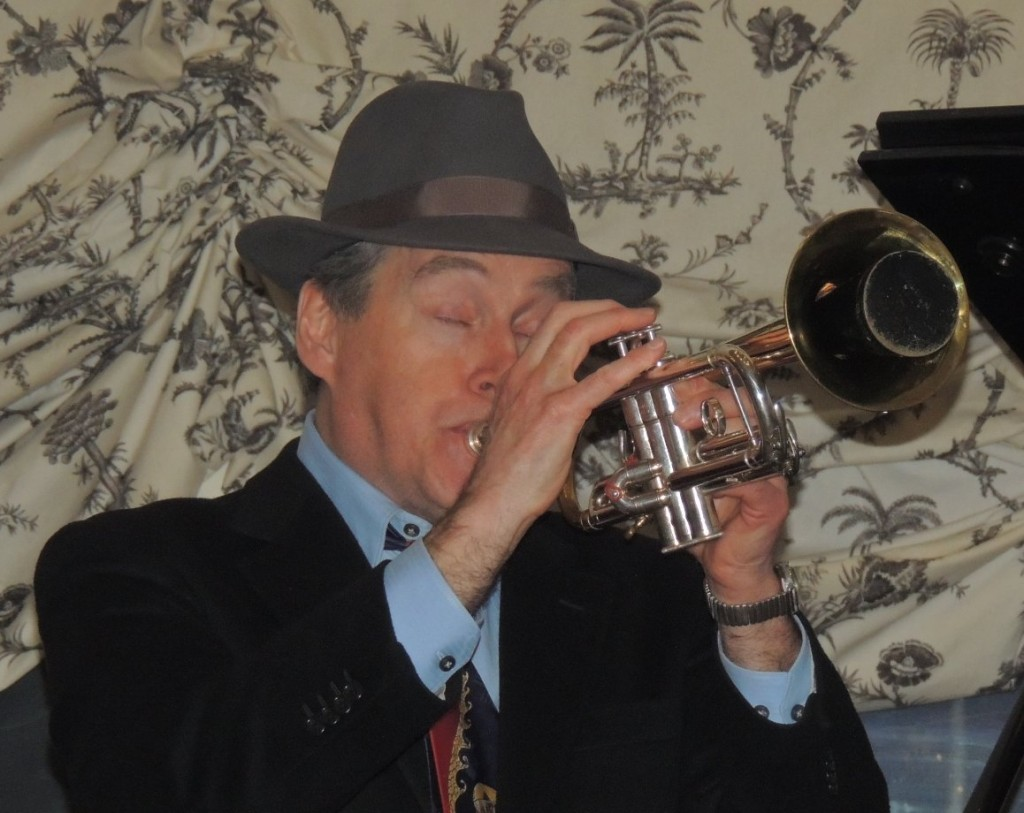 Jeff wearing fedora hat, playing trumpet