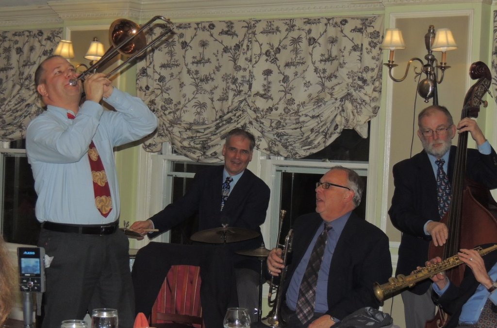 Gerry standing, trombone point in the air, Stout and Taddeo in awe