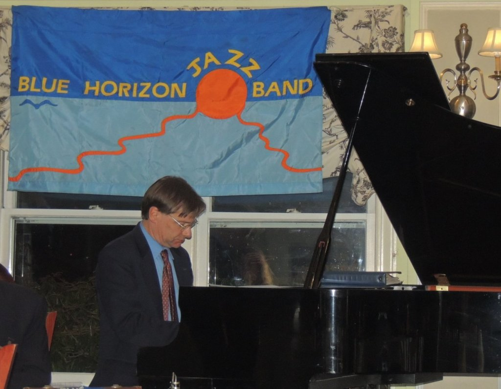 Ross on piano with Blue Horizon blue flag with large sun in middle behind him
