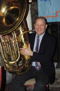 Smiling tubist with huge tuba