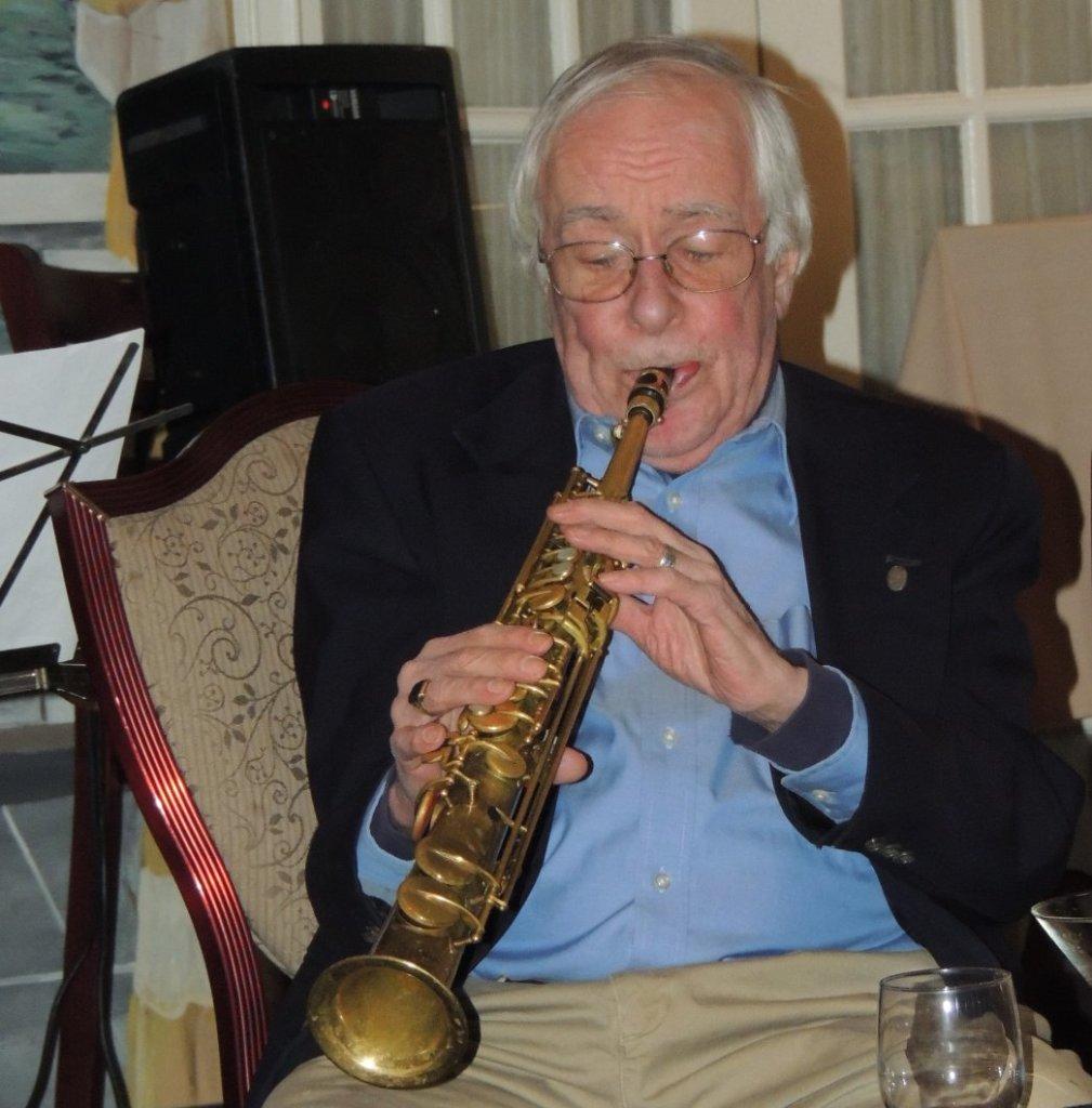 Stan sitting, playing soprano sax