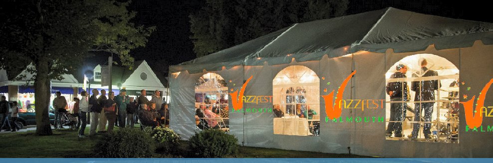 tent lit up at night with Jazz Fest logo