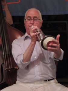Phil Person, white hair, pulled back in long tail, with muted trumpet