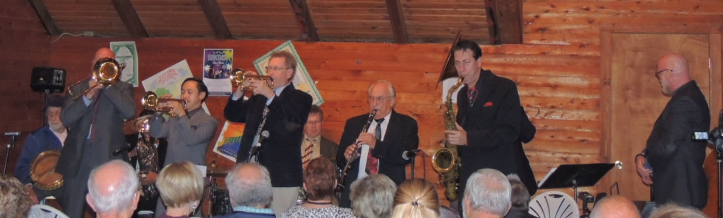 Barnhart standing with arms folded looking at brass musicians.