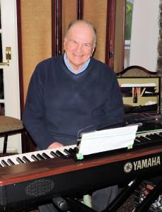 Phil at the keyboard, smiling at the camera