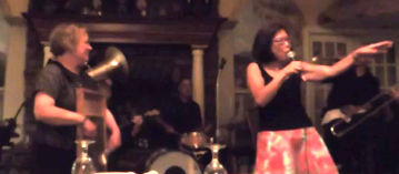 Carolyn on washboard, Elaine sing, both in front of band.