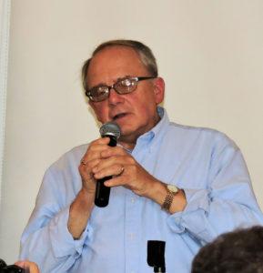 Paul at mic, gray hair and glasses