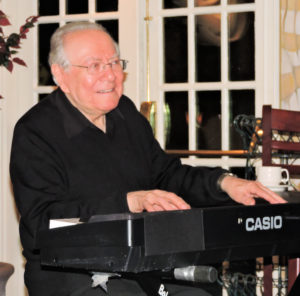 Bob Winter smiling and playing piano.