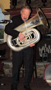 Eli standing and playing beautiful ornately carved tuba.