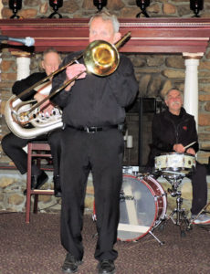 standing stage center, playing trombone, with tuba and drum in background