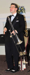 standing In tux with long tail in back, holding trombone and singing his heart out