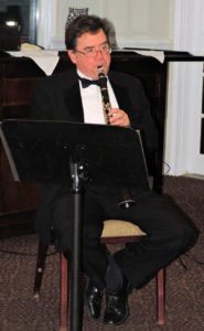 seated, playing clarinet