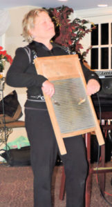 Carolyn with eyes closed playing washboard with spoons