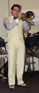 Dan Gabel with white pants and vest and wing tips playing valve trombone