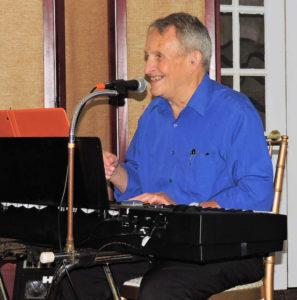 Herb at keyboard smiling and singing