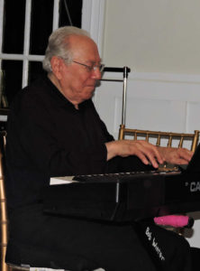 Bob playing keyboard with a big smile on his face