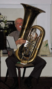 Sitting, with tuba braced on chair between his legs