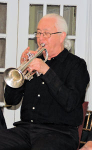 Phil with hair in long white pony tail, plays trumpet