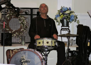 Bob, with eyes closed and head thrown back, playing snare drum.